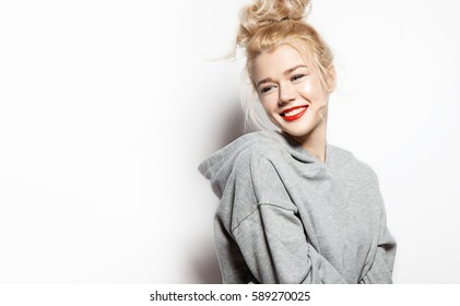 Fashionable smiling woman standing on a white background in a gray sweatshirt with a blank space and looking to side
