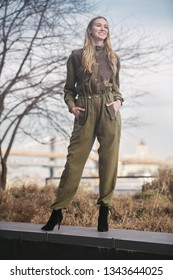 Fashionable smiling woman wearing long overalls outfit posing in the city