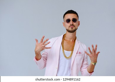 fashionable sophisticated man in a pink jacket and black trousers, wears a gold chain, the expression of emotions gestures with his hands.
