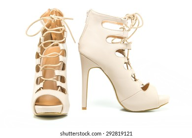 fashionable stiletto high heels ankle boots in nude color with laces, open toe and stiletto heel.
