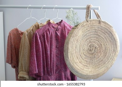 Fashionable straw bag with gypsophila flowers and colorful floral dresses on a clothing rack. Selective focus.