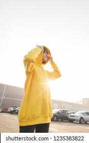 Fashionable street portrait of a girl in a yellow hoodie. Lookbook. Street fashion portrait