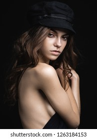 Fashionable studio portrait of a beautiful young model in black hat and sexy top on a black background. Low key.