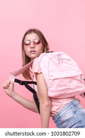 Fashionable studio of teenage style. Fashionable young girl wearing a pink t-shirt and blue shorts, holding a backpack, posing isolated on a pink background.