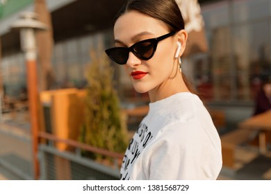 Fashionable stylish attractive woman with dark hair and bright make up walking outside in good sunny day