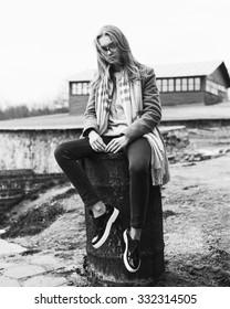 Fashionable stylish beautiful girl in sunglasses sitting on a barrel