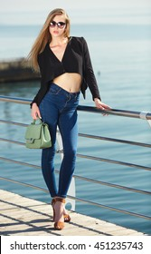 Fashionable stylish beautiful young woman wearing high waist blue jeans and original black jacket standing on an esplanade by the sea, holding green bag.