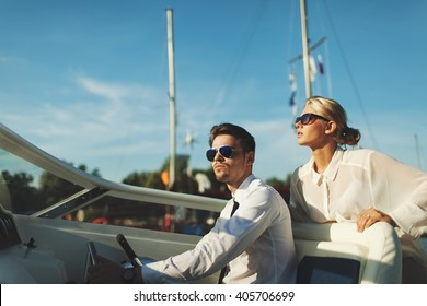 Fashionable stylish couple driving luxury yacht and posing in sunglasses with blue sky background
