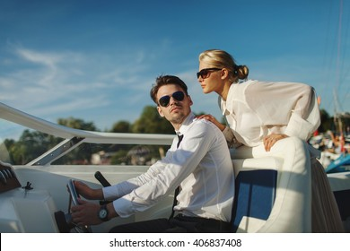 Fashionable stylish couple driving luxury motorboat yacht and posing in sunglasses with blue sky with clouds background
