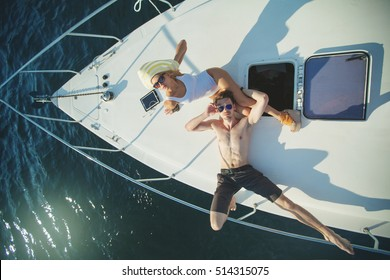 Fashionable stylish couple relaxing and lying on the deck of luxury motorboat yacht and posing in sunglasses with blue water background