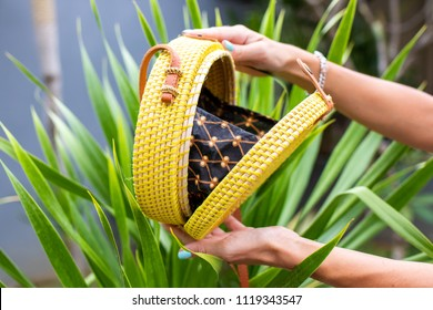 Fashionable stylish rattan bag on a tropical background. Tropical island of Bali, Indonesia. Rattan handbag.