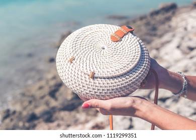 Fashionable stylish rattan bag outside. Tropical island of Bali, Indonesia. Rattan handbag.