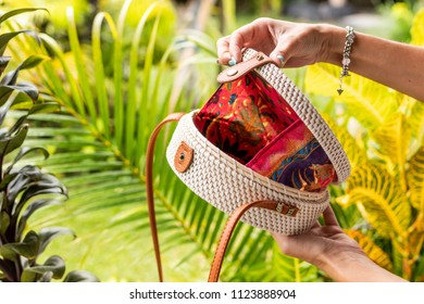 Fashionable stylish rattan bag in the tropical garden. Tropical island of Bali, Indonesia. Rattan handbag.