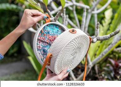 Fashionable stylish rattan bag in the tropical garden.