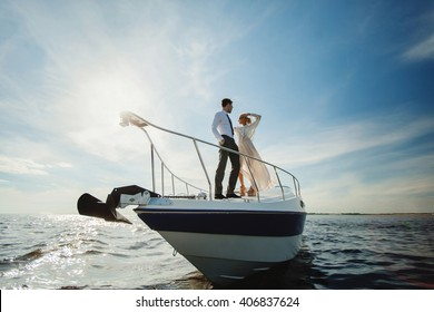 Fashionable stylish standing young couple posing on luxury motorboat yacht on blue sky with clouds and sea landscape background in daylight view from the water