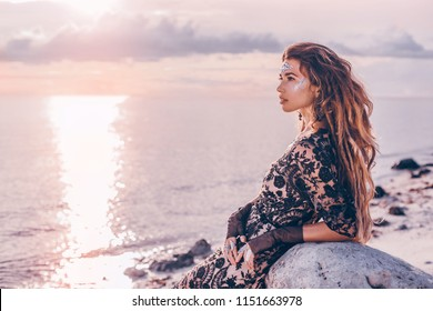 fashionable stylish woman with boho accessories on the beach at sunset