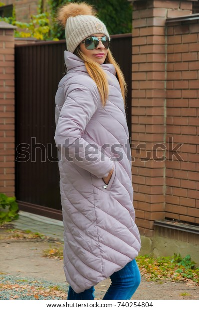 Fashionable stylish woman in a pink down jacket and woolen beige hat with fur pompon, strolls along a country road. Wonderful autumn day off in which it is nice to relax, think, dream, autumn blues.