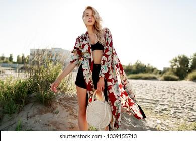 Fashionable summer image of beautiful blond female in trendy beachwear, holding straw bag.  Pretty slim girl enjoying weekends near ocean.