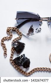 Fashionable sunglases with necklace. Fashion background.