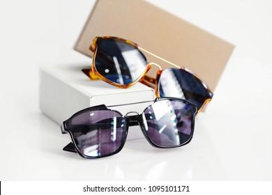 Fashionable sunglasses with box on white background