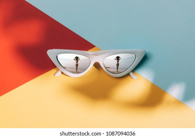 Fashionable sunglasses in on a colored background in the glasses which reflects a girl on the beach