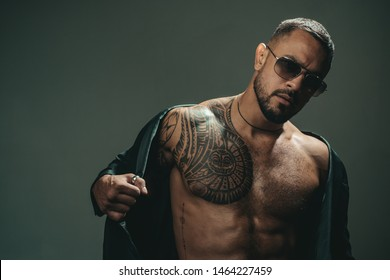 Fashionable tattoo. Muscular hispanic man with tattoo on chest. Strong latino man with tattoo on skin. Tattooed guy with muscle torso and tattoo.
