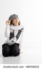 Fashionable teenage girl in a cap. Joyful teen girl in casual clothes. Active lifestyle. Youth fashion. Studio shot. thoughtful girl sits on lap and eyes hidden under cap