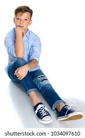 Fashionable teenager boy sits on the floor on a white background. The concept of a happy childhood, the harmonious development of the child in the family. Isolated.