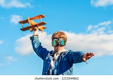Fashionable teenager in pilot glasses with an airplane in his hands. Concept purpose, adventure, travel, freedom