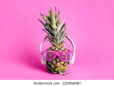 Fashionable trendy pineapple fruit with headphones and sun glasses listen to the music over bright pastel pink background. Cool hipster ananas with funny face. Summer holiday and beach party concept