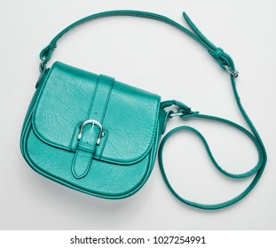 Fashionable turquoise leather bag on a white background. Top view, women's accessories.