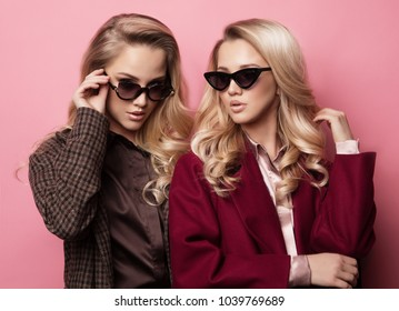Fashionable two blond women in coat with sunglasses. Fashion autumn winter photo.