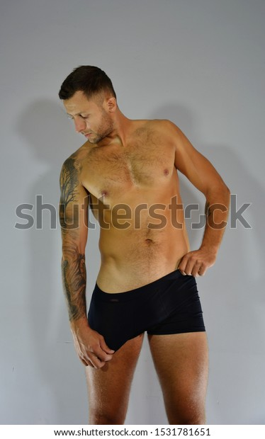 Fashionable and undressed young man in black underwear with stylish