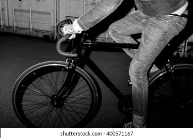 Fashionable urban dweller on fixed-gear bicycle at night. Black and white lifestyle