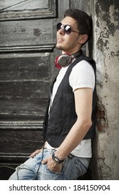Fashionable urban young man portrait in old city street.