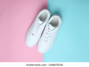Fashionable white sneakers on a colored pastel background, minimalism, top view, creative layout
