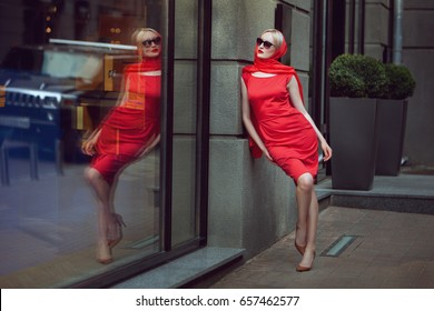 Fashionable woman admires herself in the reflection of the shop window.