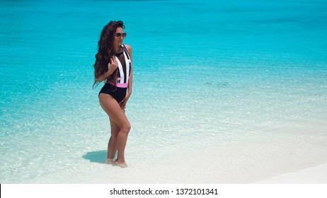 Fashionable Woman in bikini suntanning on tropical beach. Pretty slim girl posing on exotic island by beautiful turquoise ocean.  Brunette model in trendy swimwear resting in Maldives lagoon.