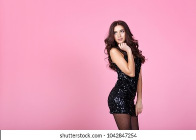 fashionable woman in black evening dress posing on pink background. copy space