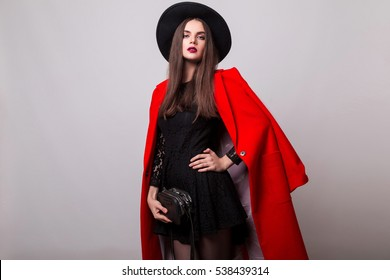 Fashionable woman in bright red coat and black hat posing in studio, looking at camera. cold season. Autumn or winter look.