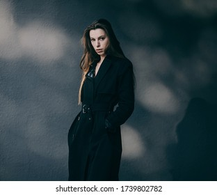 Fashionable woman in coat and long hair in city. Fashion autumn photo