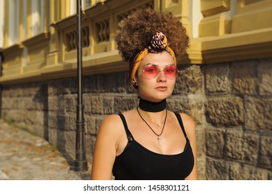 Fashionable woman in downtown. Eccentric girl with red sunglasses and curly hair. Girl in black dress. Retro style concept.