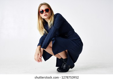 fashionable woman in a dress glasses squatted on a squat on a white isolated background beauty fashion style