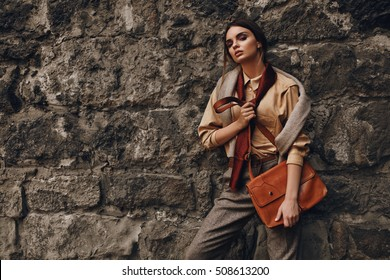 Fashionable Woman In Fashion Clothing. Beautiful Sexy Girl In Elegant Stylish Fall Clothes: Shirt, Scarf, Pants, Pullover, Leather Bag Posing Near Rock Wall Outdoors In Street In Autumn Or Spring