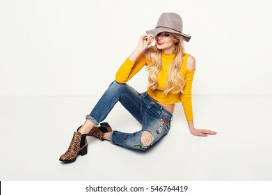 Fashionable woman in a hat, boots and jeans, posing in a studio. Fashion photo