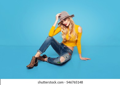 Fashionable woman in a hat, boots and jeans, posing in a studio over blue background. Fashion photo