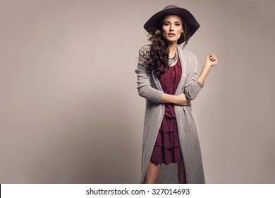 Fashionable woman in a hat, dress and long grey sweater, accessories, high heels, posing in studio. Fashion autumn photo