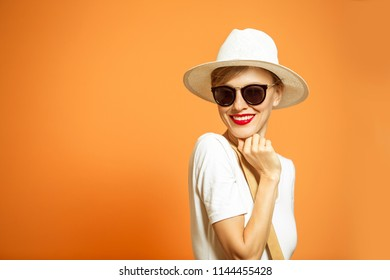 Fashionable woman in a hat and sunglasses, accessories, posing in studio over vibrant color background, copy space. Fashion summer or autumn photo