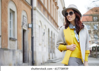 Fashionable woman in a hat, sunglasses, yellow sweater, walking in the street. Fashion spring photo