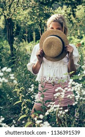 Fashionable woman hiding behind straw hat